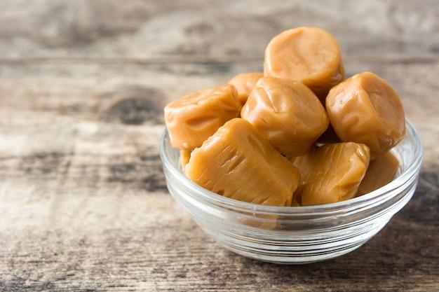 Karmelowe cukierki toffi w kryształowej misce na drewnianym stole