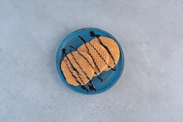 Karmelowe gofry ozdobione sosem czekoladowym na niebieskim talerzu.