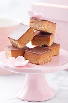 Karmelowo-biszkoptowe ciastko gryzie deser na różowym stojaku z filiżanką i pudełkiem prezentowym