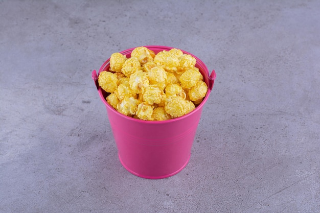 Karmelowy popcorn podawany w małym wiaderku na marmurowym tle. zdjęcie wysokiej jakości