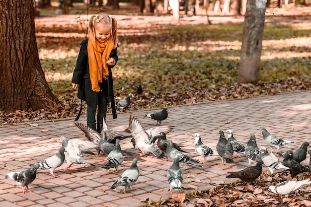 Karmienie gołębi w jesiennym parku przez małą dziewczynkę w jesiennych ubraniach