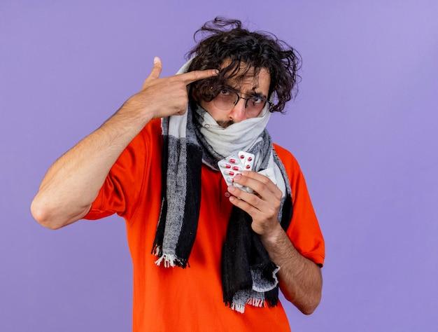 Karmiony młody chory mężczyzna w okularach i szaliku trzymający pigułki medyczne robi gest samobójczy patrząc na przód odizolowany na fioletowej ścianie z miejscem na kopię