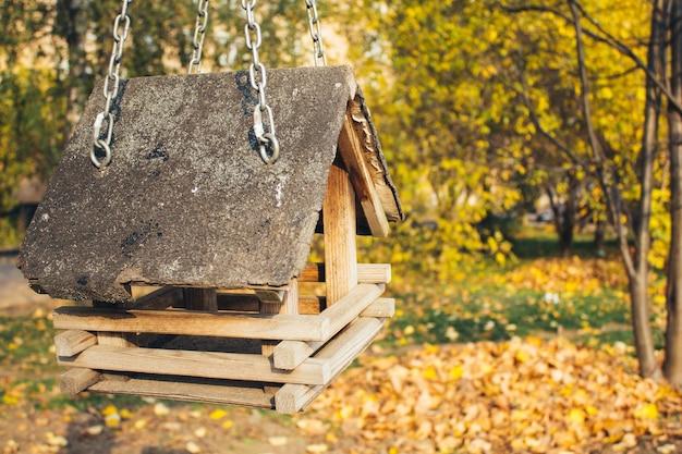 Karmniki dla ptaków. klasyczny leśny karmnik dla ptaków i wiewiórek jako mały dwuspadowy domek na drzewie.