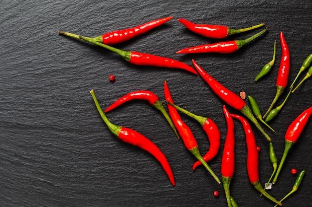 Karmowego korzennego prezentaci tła czerwony chili i zieleni chili na czerni łupku wsiadamy
