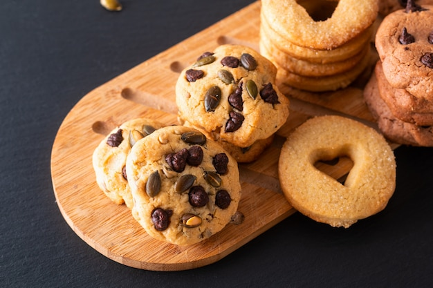 Karmowego pojęcia masła domowej roboty cukrowi ciastka na drewnianej desce na czerń łupku kamienia talerzu z kopii przestrzenią