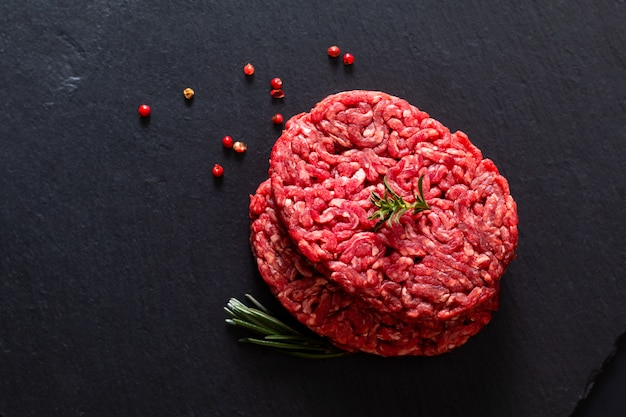 Karmowego pojęcia wołowiny trawy organicznie zmielony surowy lub mielony wołowiny karmy hamburger na czerń łupku kamieniu z kopii przestrzenią