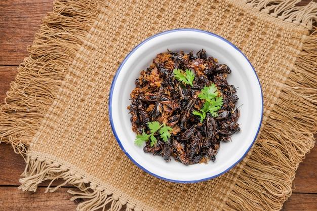 Karmowy insekt, smażący krykiet w żelaznym pucharze na drewnianym stole, tajlandzki jedzenie.