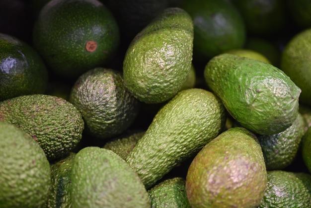 Karmowy owocowy świeży zielony avocado tło. świeży wzór awokado na sprzedaż na rynku