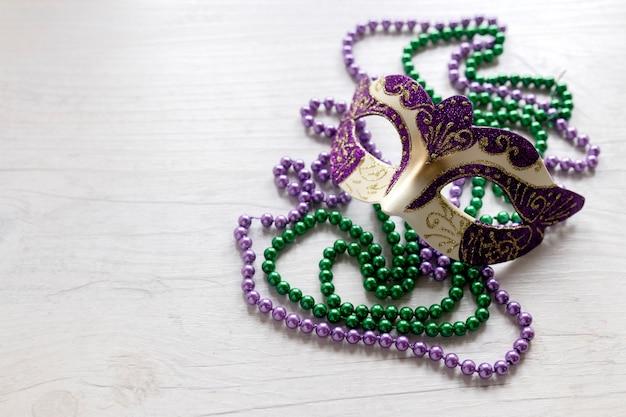 Karnawałowa maska na koralikowych naszyjnikach