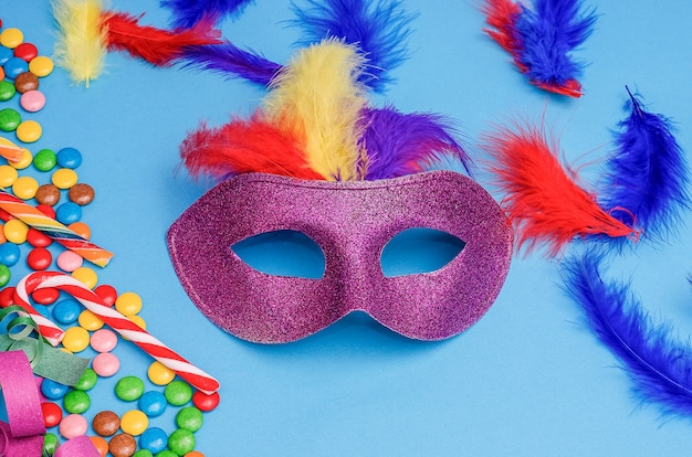 Karnawałowa maska na niebieskim tle z mardi gras, brazylijskim, weneckim karnawałem