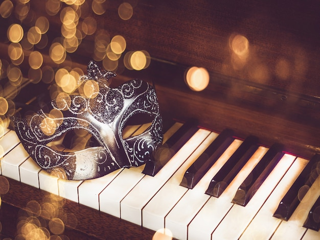 Karnawałowa maska na tle klawiszy fortepianu