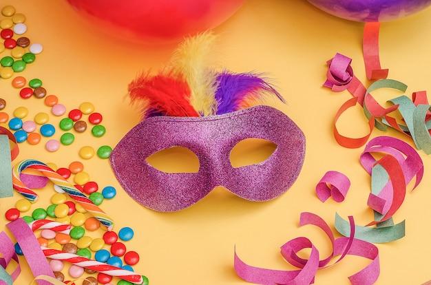 Karnawałowa maska na żółtym tle z mardi gras, brazylijskim, weneckim karnawałem