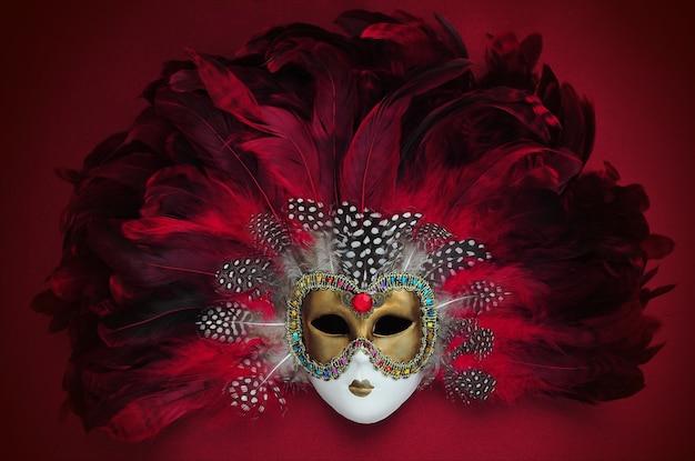 Karnawałowa maska z czerwono-fioletowymi piórami