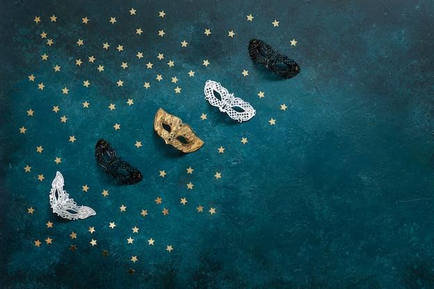 Karnawałowe maski i złote brokaty konfetti. widok z góry, zamknij się na niebieskim tle