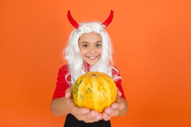 Karnawałowy świąteczny strój czarownicy. dziecko z dynią. dziecko świętować jesienne wakacje z tradycyjnym jedzeniem. nastolatka w diabelskie rogi świętować halloween. wesołego halloween. cukierek albo psikus.