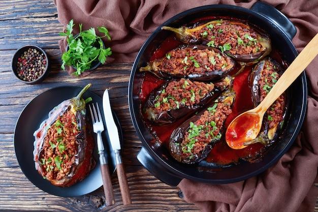 Karniyarik - nadziewane bakłażany, bakłażany z mieloną wołowiną i warzywami zapiekane w sosie pomidorowym na talerzu widelcem i nożem, kuchnia turecka, widok poziomy z góry, zbliżenie, flatlay