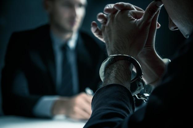 Karny mężczyzna z kajdankami w pokoju przesłuchań