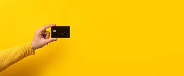 Karta bankowa w ręku na żółtym tle, makieta panoramiczna