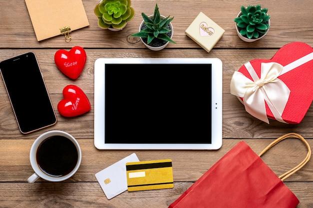 Karta debetowa, wybiera prezenty, dokonuje zakupu, tablet, filiżanka kawy, dwa serduszka
