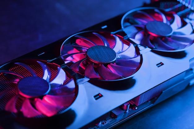 Karta graficzna z rzędem wentylatorów z cyjanowo fioletowym podświetleniem w futurystycznym designie. wydajna karta graficzna do gier do gier wideo i kopania kryptowalut. klawisz ciemny, widok z góry