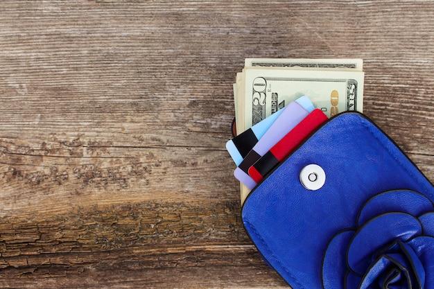 Karta kredytowa i dolary w portfelu na drewnianym