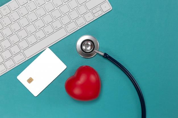 Karta kredytowa i stetoskop z czerwonym sercem
