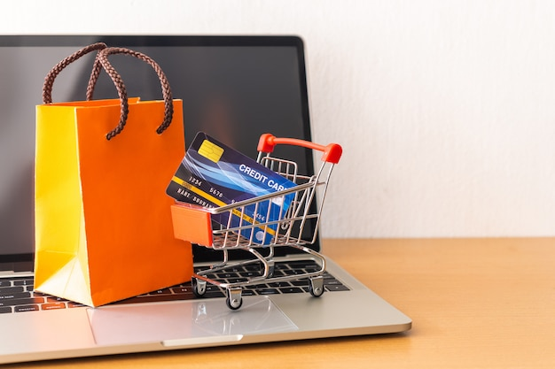 Karta kredytowa i wózek supermarket i pomarańczowa papierowa torba na stół z drewna. koncepcja zakupów