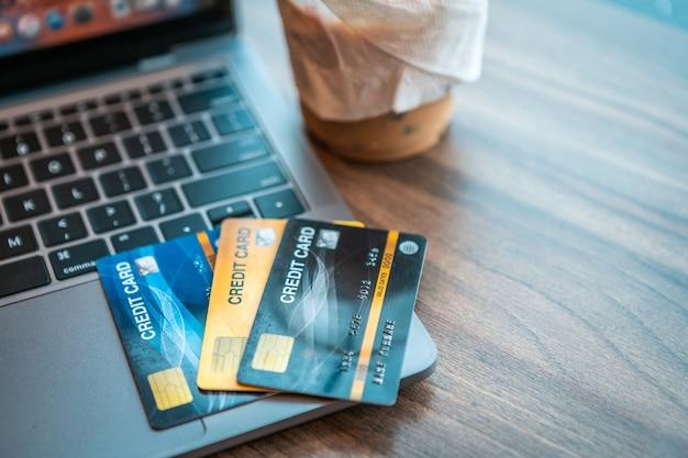 Karta kredytowa laptopa i filiżanki kawy na drewnianym stole w kawiarni kopia tło, koncepcja bankowości internetowej