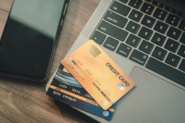 Karta kredytowa laptopa, smartfona i filiżanki kawy na drewnianym tle, koncepcja bankowości internetowej