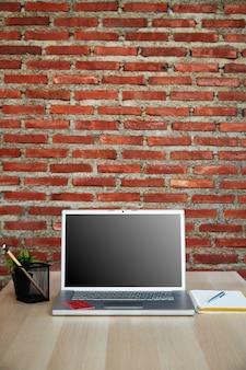 Karta kredytowa na laptopie z pustym ekranem na biurku i ścianą z czerwonej cegły działa w domu lub podczas zakupów online