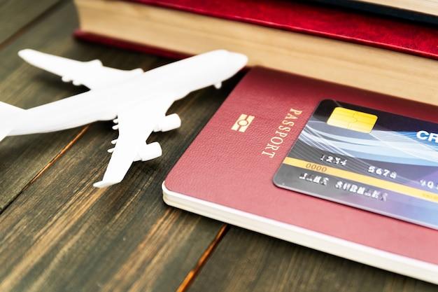 Karta kredytowa umieszczona na modelu paszportu i samolotu na drewnianym stole, przygotowanie do koncepcji podróży