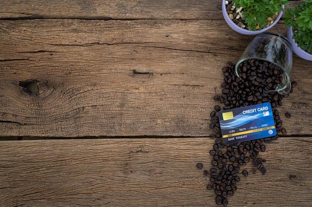Karta kredytowa umieszczona na ziarnach kawy w widoku z góry stołu