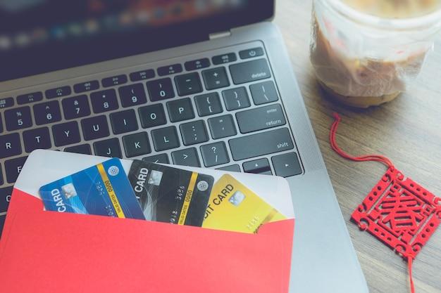 Karta kredytowa w czerwonej kopercie na laptopie z napisem w języku chińskim błogosławieństwa to wiosna z kawą izolować na drewnianym tle biurko dla premii chińskiego nowego roku