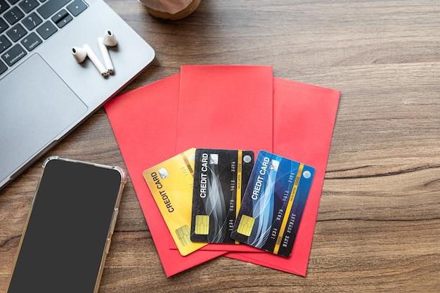 Karta kredytowa w czerwonej kopercie, słuchawkach, smartfonie laptop z kawą izolat na drewnianym biurku tła dla premii chińskiego nowego roku