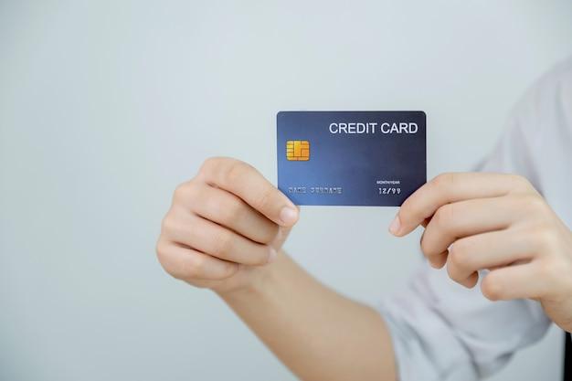 Karta kredytowa w dłoni bizneswomanu do zakupów online z domu, płatności e-commerce, bankowości internetowej