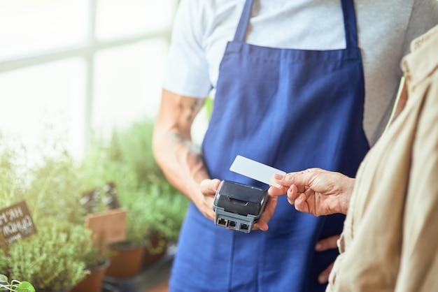 Karta kredytowa w kobiecej dłoni w pobliżu płatnego terminala