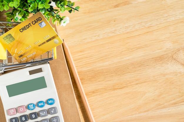 Karta kredytowa w koszyku z notebookiem, ołówek, doniczka, kalkulator na drewnianym tle, bankowość internetowa widok z góry ze stołem biurowym.