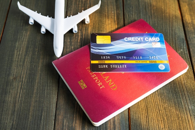 Karta kredytowa założona na paszport i model samolotu na drewnianym stole, koncepcja przygotowania do podróży