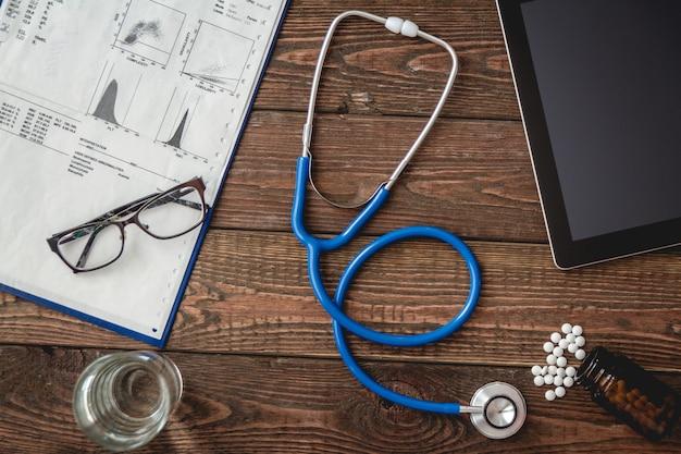 Karta medyczna pacjenta, stetoskop, tablet na drewnianym stole widok z góry
