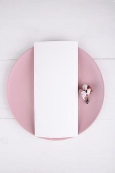 Karta menu z kwitnącą gałązką migdałów na różowym talerzu, element projektu na ślub.