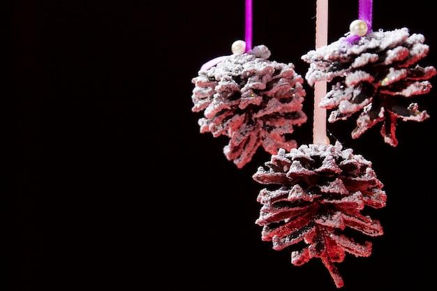 Karta noworoczna. ośnieżone szyszki na czarnym tle