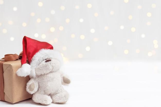 Karta noworoczna. uroczysty miś w czerwonym kapeluszu w pobliżu prezentu na tle świateł.