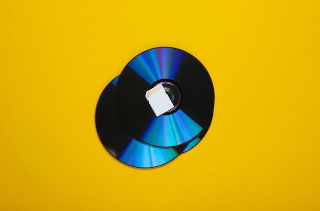Karta pamięci sd, dyski cd na żółtym papierze o geometrycznych kształtach