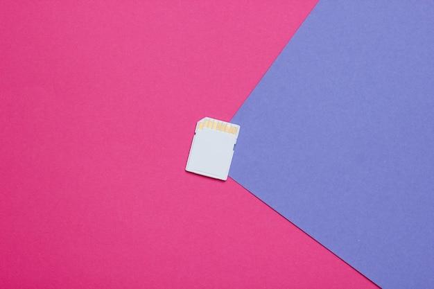 Karta pamięci sd na kolorowym papierze o geometrycznych kształtach