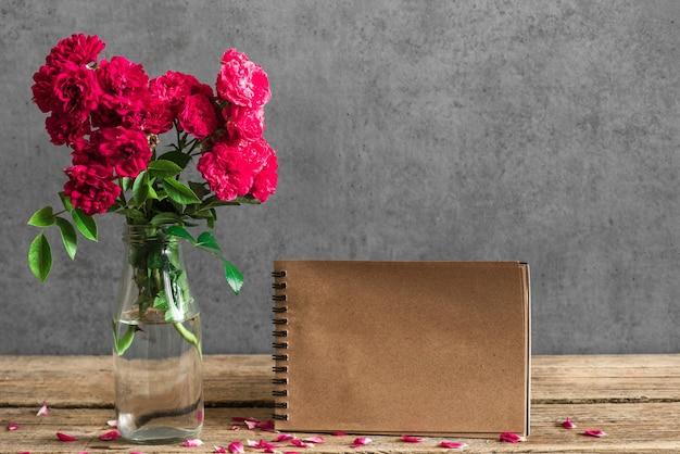 Karta papieru rzemiosła ślub z bukietem czerwonych kwiatów róży w wazonie.