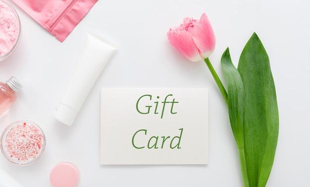 Karta podarunkowa z różowym kwiatkiem na białym tle z salonu kosmetycznego perfumerii. karta podarunkowa prezent dla kobiety. bon-niespodzianka na dzień matki, happy birthday, rocznicę, żonę.