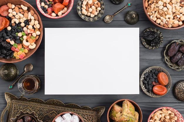 Karta ramadan otoczona tradycyjnymi suszonymi owocami; daktyle; herbata i bakława na stole