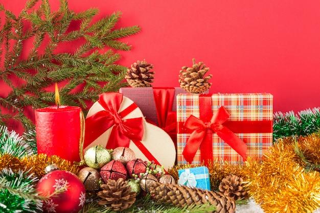 Karta świąteczna lub noworoczna. płonącą świeczkę, stożki, pudełka na prezenty, kule ze świecidełkiem i gałąź choinki na śniegu