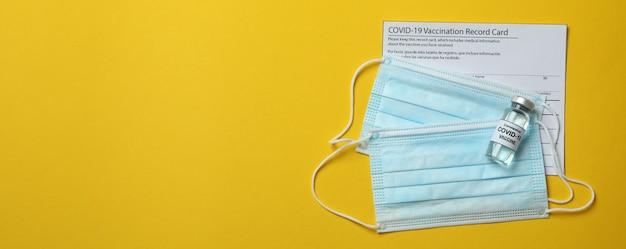 Karta szczepień, szczepionki i maski na żółtym tle