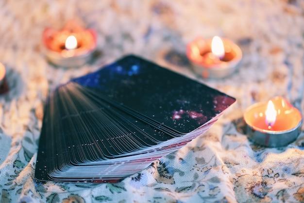 Karta tarota z blaskiem świec na tle ciemności dla astrologii okultystycznej magii / magicznych duchowych horoskopów i wróżki palmowej